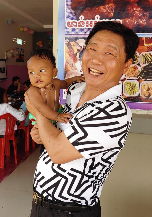 김일석 청실회 총재가 캄보디아 해외 봉사활동 중 현지 어린이를 안고 환하게 웃고 있다.