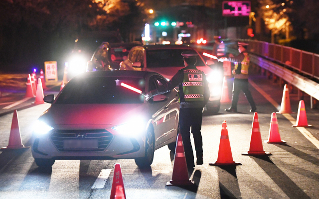 김해중부경찰서 경찰들이 지난 3일 밤 삼계동 생림대로에서 S자형 고깔을 세워놓고 음주 단속을 하고 있다./김승권 기자/