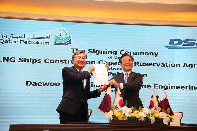 대우조선해양 이성근(왼쪽) 대표이사와 성윤모 산업통상자원부 장관이 서명한 LNG선 슬롯 예약 약정서를 들어보이며 기뻐하고 있다. /대우조선해양/