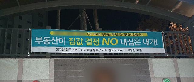 도내 한 아파트에 걸린 집값 관련 현수막./독자 제공/