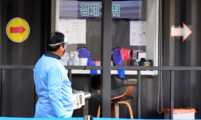 29일 오후 창원시 마산보건소 선별진료소에서 보건소 관계자가 선별진료소 일대를 방역하고 있다./성승건 기자/